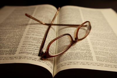 reading, glasses, atop, pages, open, dictionary, book