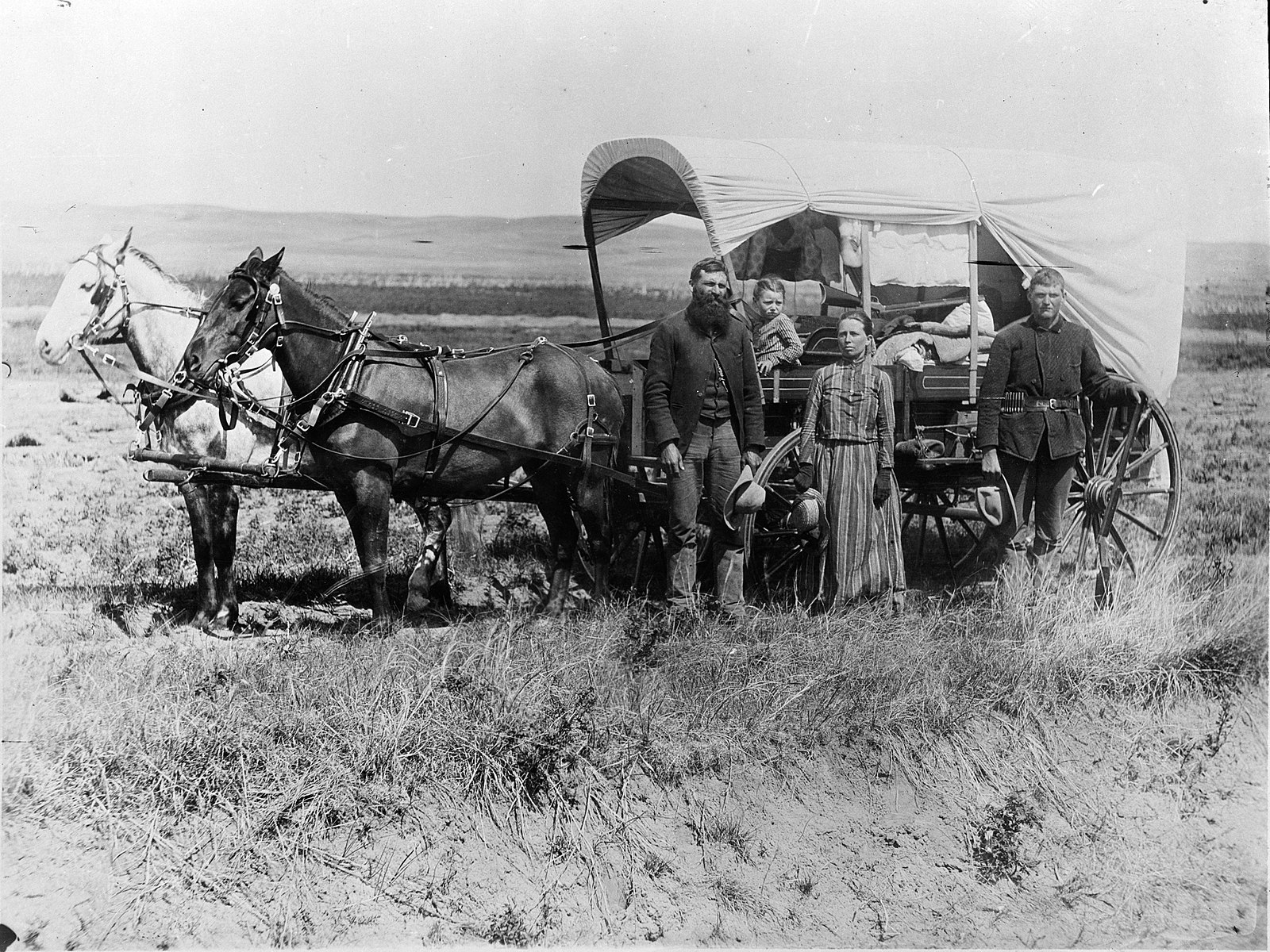 1600px-photograph_of_a_family_with_their_covered_wagon_during_the_great_western_migration2c_1866_-_nara_-_518267